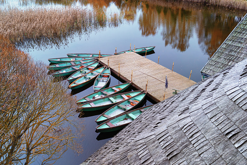 Fishing green wooden boats at the pier on a background of a wooden roof of a house on a lake in autumn