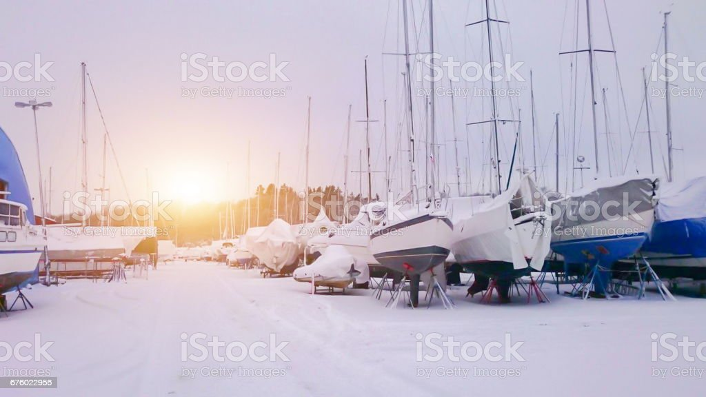 Fishing boats boat in the small harbor during winter time. Ice, snow and sunshine stock photo