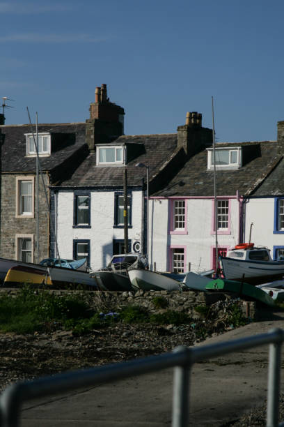 Fishing boats in a port in front of terraced houses, Dumfries an stock photo