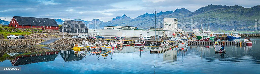 Fishing boats in colourful port tranquil ocean fjord harbour Iceland stock photo