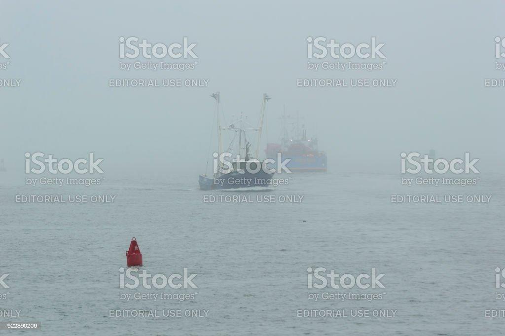 Fishing boats in fog stock photo