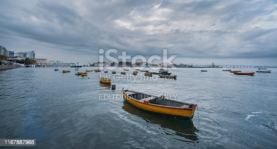 Rio de Janeiro, Brazil - August 17 2013: Boats and fishermen in front of rio de janeiro, next to the ferry terminal and Niteroi bridge