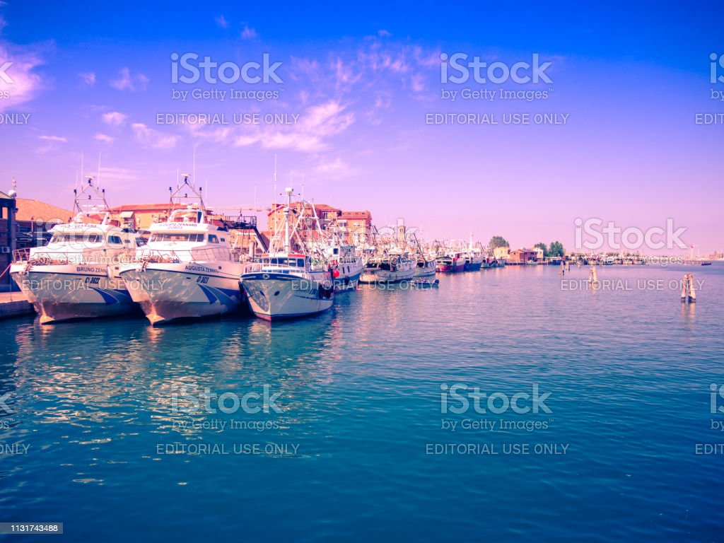 Fishing boats moored in a canal in Chioggia, Italy. stock photo