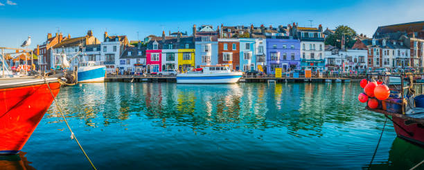 fishing boats moored in busy harbour colourful cottages weymouth dorset - weymouth stock photos and pictures
