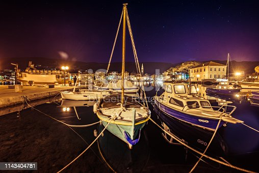 Fishing boats moored in small marina at night
