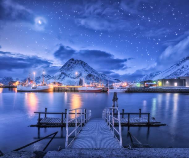 Angelboote/Fischerboote in der Nähe von Pier auf dem Meer vor schneebedeckten Bergen und Sternenhimmel mit Mond in der Nacht in Lofoten Inseln, Norwegen. Winterliche Landschaft mit Brücke, Schiff, Gebäude, Beleuchtung, Felsen und Wolken – Foto