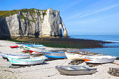 Small fishing boat on the famous pebble beach and cliffs of Etretat, commune in the Seine-Maritime department in the Haute-Normandie region in northwestern France