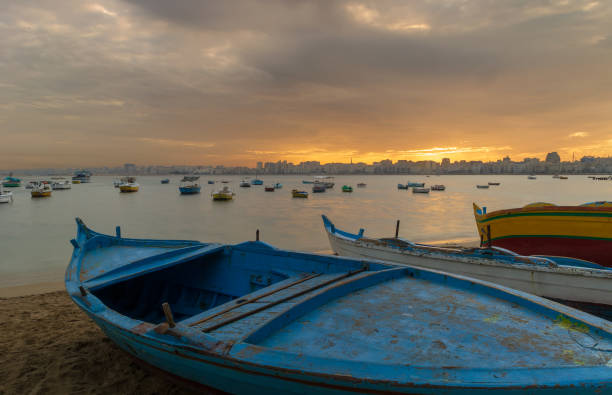 Fishing boats on the beach at dusk with Alexandria skyline in far distance and colorful sky at sunrise, Egypt stock photo