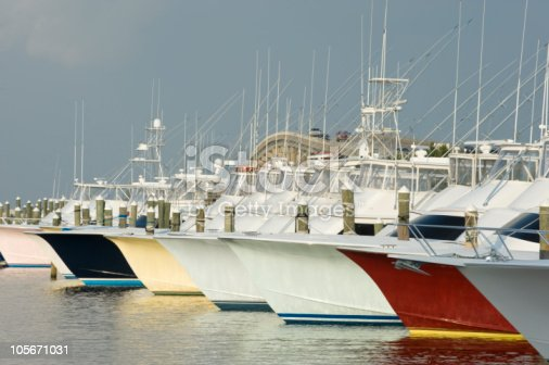 Charter fishing boats are docked at Pirates Cove Marina with their bows in a line in the outer banks, North Carolina. A bridge leading over to Nags Head, NC is in the background.