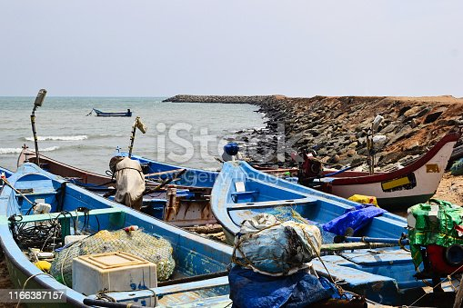 Old motor fishing boats on the beach. Fishermen vessels in a small harbor. Kanyakumari, Tamil Nadu, India.