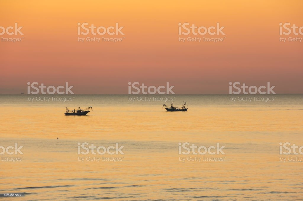 Fishing boats pull their nets at the sunrise. Adriatic cost. Emilia Romagna. Italy stock photo