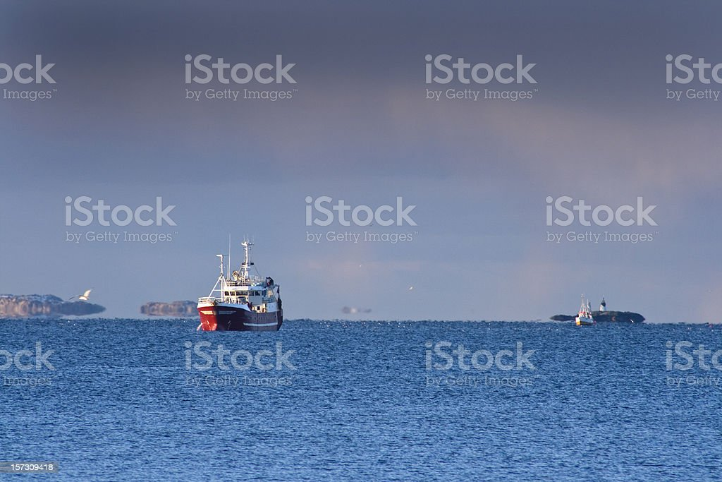 Fishing boats returning home after a mission on open seas royalty-free stock photo
