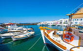 Fishing boats tied up at a dock in Naoussa port, Paros, Greece. Typical fishing boats and small yachts anchored in harbour
