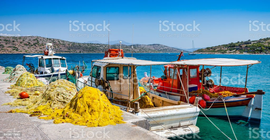 Fishing boats with nets at the pier in the village of Plaka in Crete stock photo