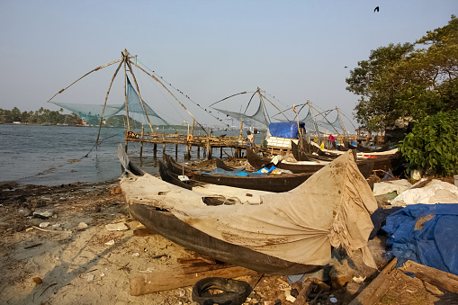 Fort Cochin, Kerala, India - January 2014: Fishing boats with traditional chinese fishing nets on a beach in the town of Fort Kochi.