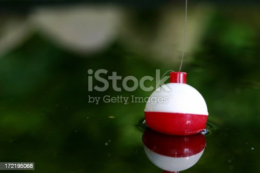 Photo of a fishing cork in a pond.  Focus is on the top of the bobber were the fishing line is attached.  Bobber is also reflected in the water.