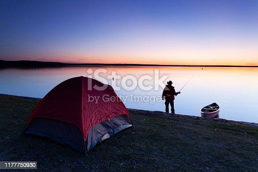 Man fishing, camping, Prince Albert National Park, Saskatchewan, Canada. Image taken from a tripod.