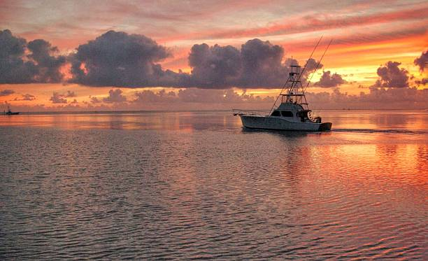 Fishing charter departs A fishing charter boat leaves very early in the morning from the Florida Keys fishing stock pictures, royalty-free photos & images