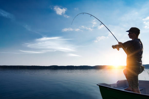 Fishing concepts. fishing rod lake fisherman men sport summer lure sunset water outdoor sunrise fish - stock image fisherman stock pictures, royalty-free photos & images