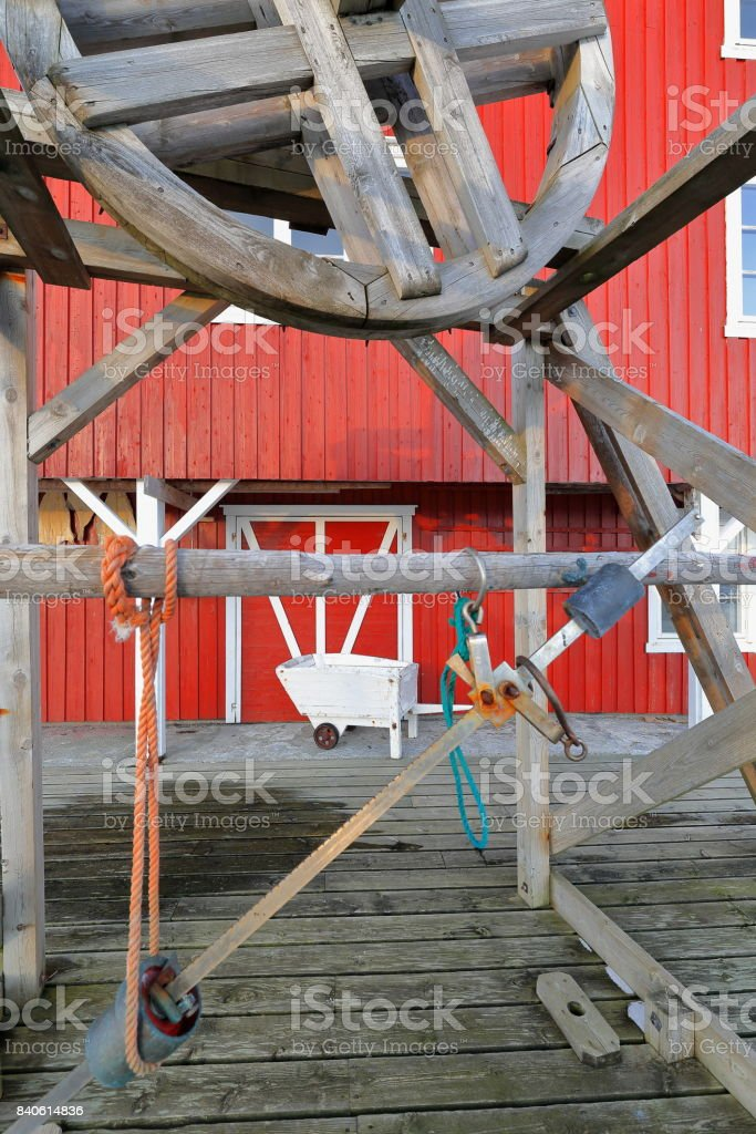 Fishing devices-red cottage or rorbu-wooden wheelbarrow. A i Lofoten-Sorvagen-Nordland-Norway. 0335-2 stock photo