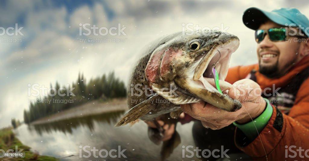 Fishing. Fisherman and trout. Dramatic. stock photo
