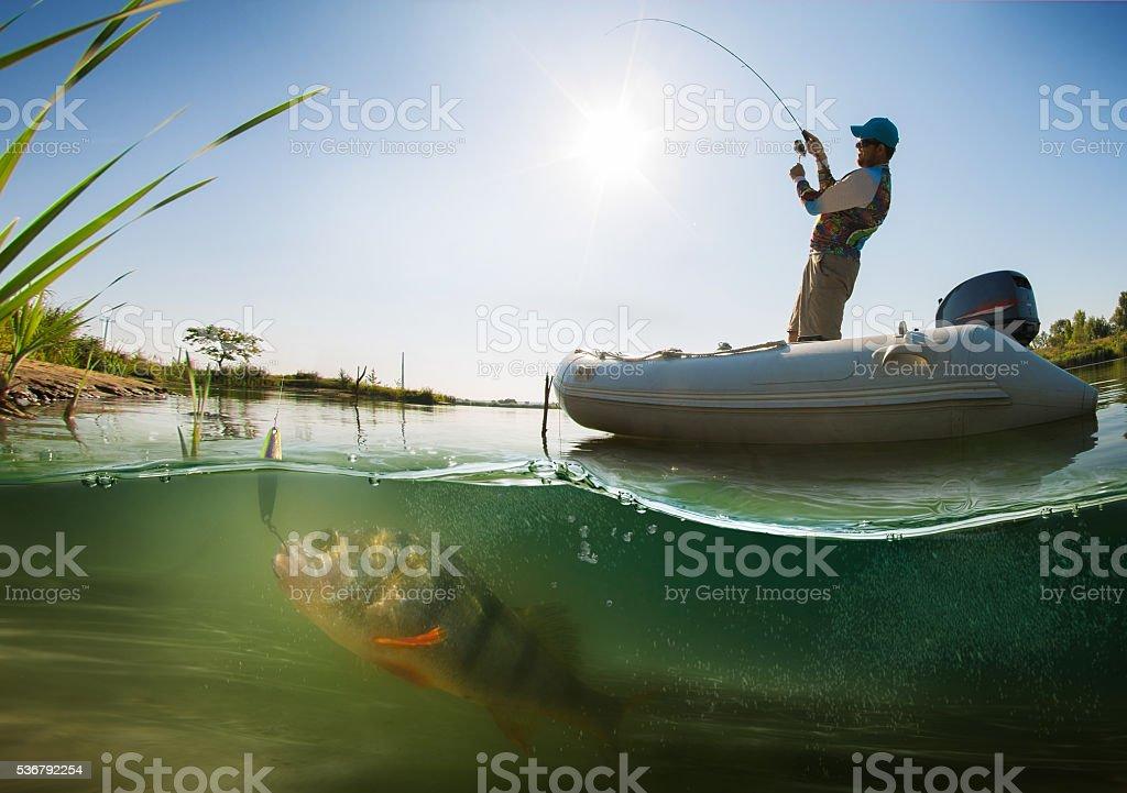 Wędkowanie. Rybaka na łodzi. Podwodne widok - Zbiór zdjęć royalty-free (Brzeg wody)