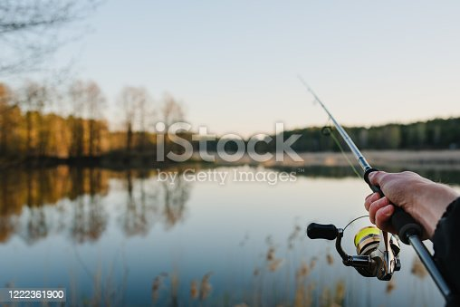 951984746 istock photo Fishing. Fisherman with rod, spinning reel on the river bank. Fishing for pike, perch, carp. Fog against the backdrop of lake. background Misty morning. wild nature. Article about fishing day. 1222361900
