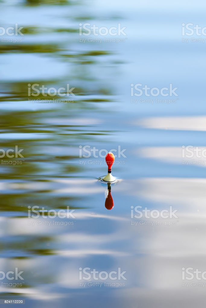 Fishing float on water with waves and beautiful reflection stock photo