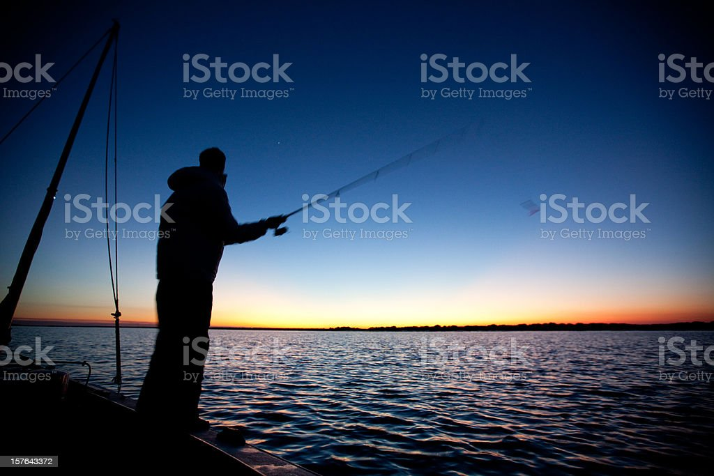 Fishing from a sailboat at sunset royalty-free stock photo