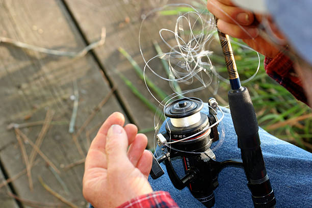 Fishing frustration Fisherman trying to untangle fishing line. fishing reel stock pictures, royalty-free photos & images