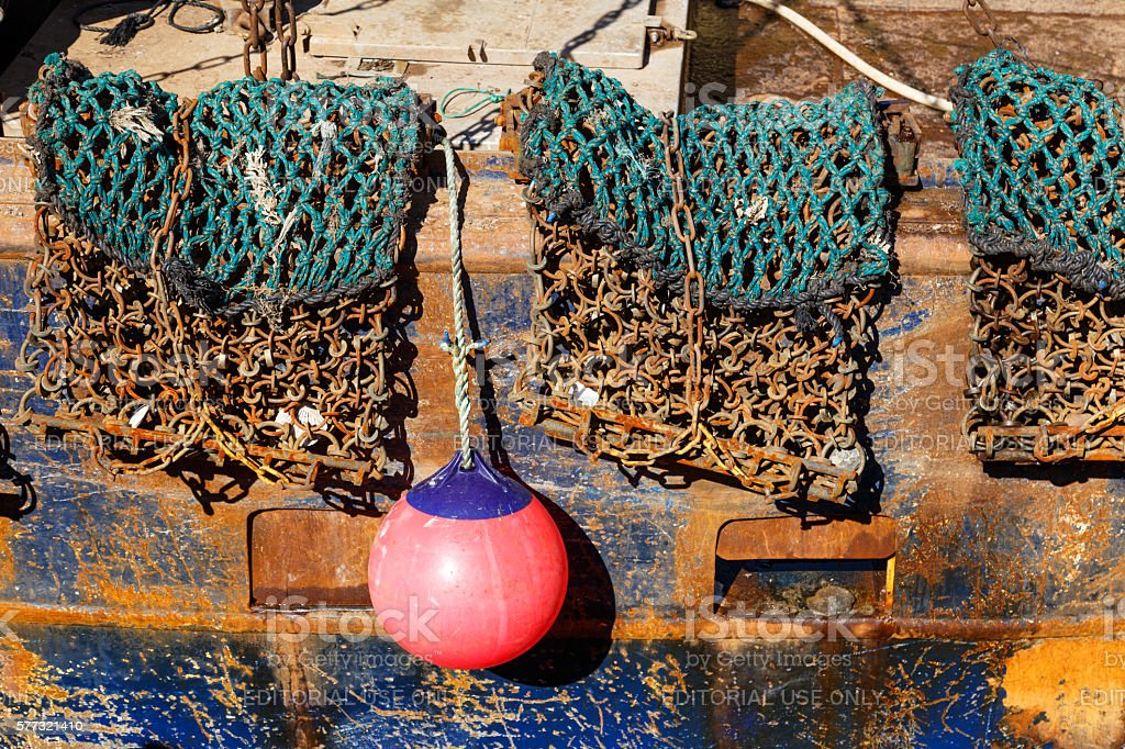 Fishing gear and buoy hanging off the side of trawler stock photo