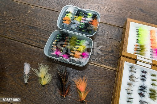 864720746 istock photo Fishing gear, set by river for fly fishing on an old wooden table 823374882