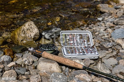 864720746 istock photo Fishing gear, set by river for fly fishing on an old wooden table 823375102