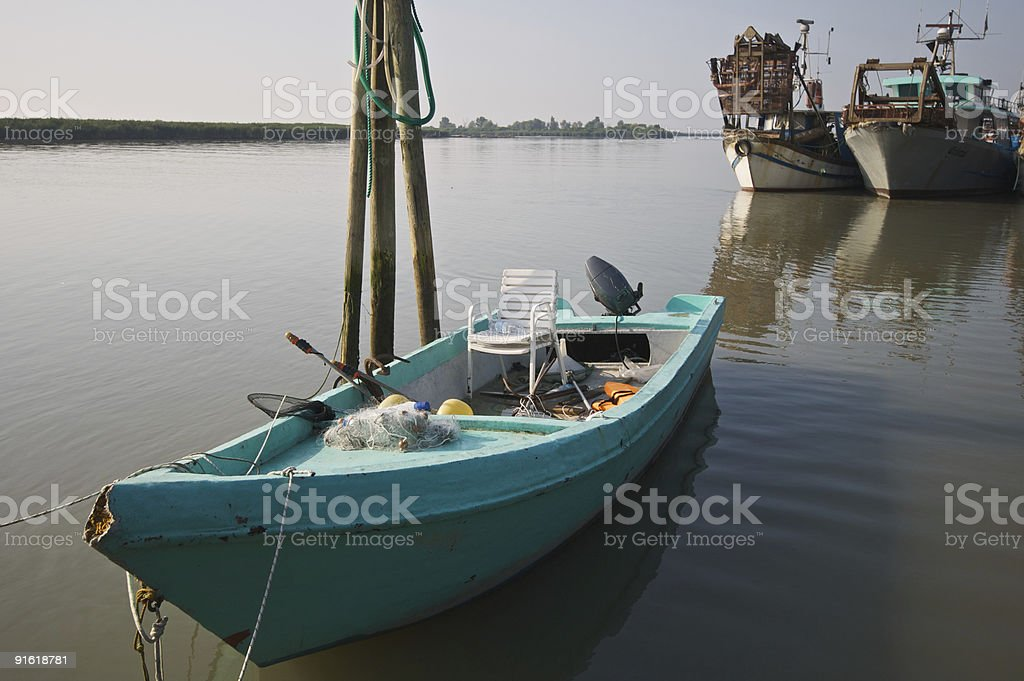 Fishing green boat in early morning sun light stock photo
