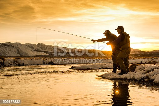 Fishing Guide Pointing Out A Trout at sunset