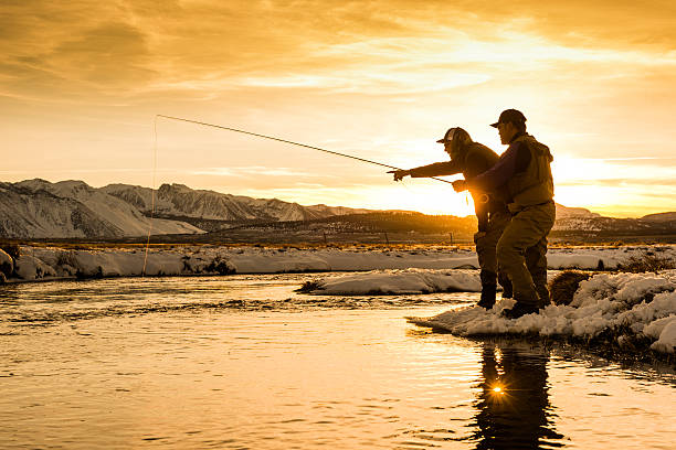 Fishing Guide Pointing Out A Trout At Sunset stock photo