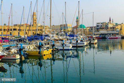 Acre: Fishing boats, yachts with and nearby monuments, in the fishing harbor in the old city of Acre (Akko), Israel. Acre was a major harbor city for many centuries