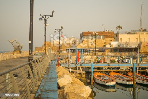 Acre: Fishing boats, yachts with and nearby monuments, at sunrise in the fishing harbor in the old city of Acre (Akko), Israel. Acre was a major harbor city for many centuries