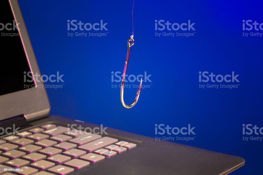 fishing hook above laptop stock photo