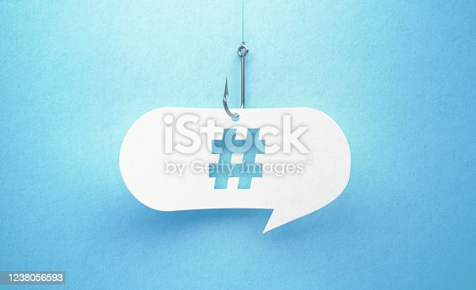 Fishing hook and hashtag symbol drawn white chat bubble on blue background. Horizontal composition with copy space. Phishing concept.