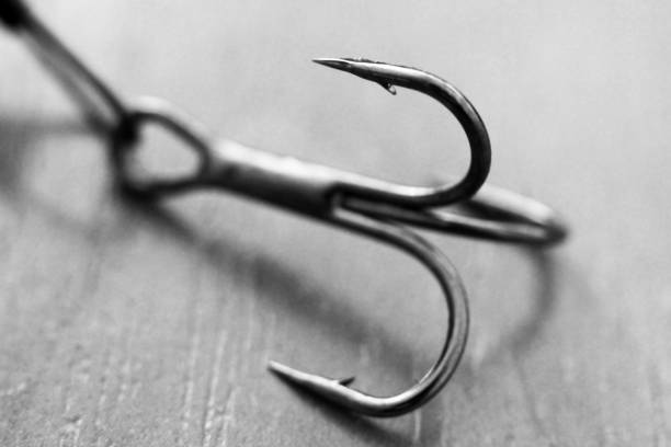 Fishing hook on wooden background, macro Fishing hook on wooden background, so close fishing hook stock pictures, royalty-free photos & images