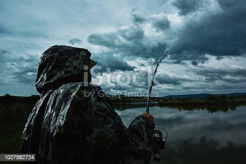 senior man in rainy day fishing with rain coat on him.
