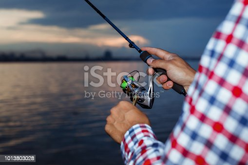 115874504istockphoto Fishing in the river at sunset. 1013803028
