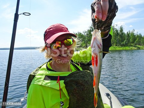 914030378istockphoto Fishing is a great catch. Caught fish in the hands of a happy fisherman. 1143084555