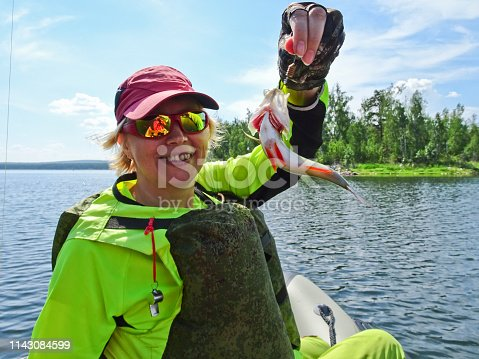914030378istockphoto Fishing is a great catch. Caught fish in the hands of a happy fisherman. 1143084599