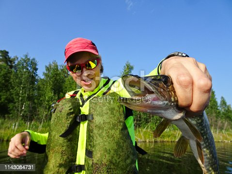 914030378istockphoto Fishing is a great catch. Caught fish in the hands of a happy fisherman. 1143084731