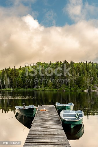 A coffee cup with a towel left on a wharf with fishing boats on a lake in a forest of Lanaudiere area in Quebec during the fishing season.