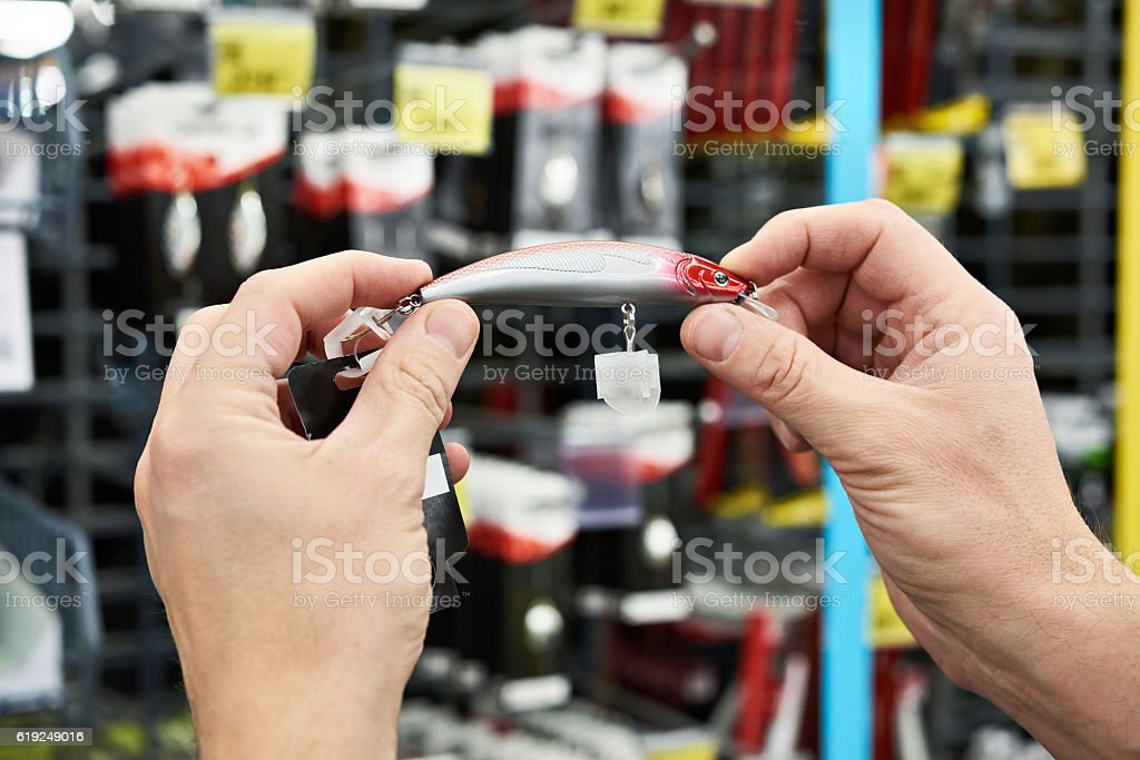 Fishing lure bait with hook in hands man in store stock photo