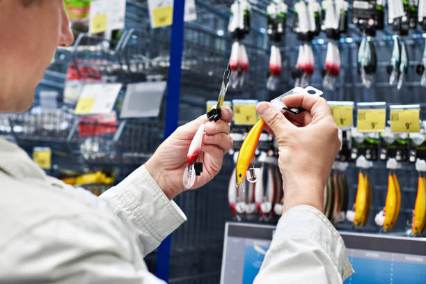 Fishing lure baits in hands man in store Fishing lure baits in the hands of man in the store fishing bait stock pictures, royalty-free photos & images