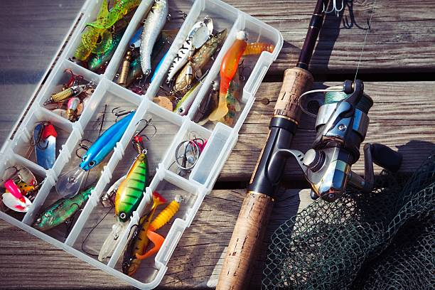 Fishing Lures in tackle boxes with spinning rod and net stock photo
